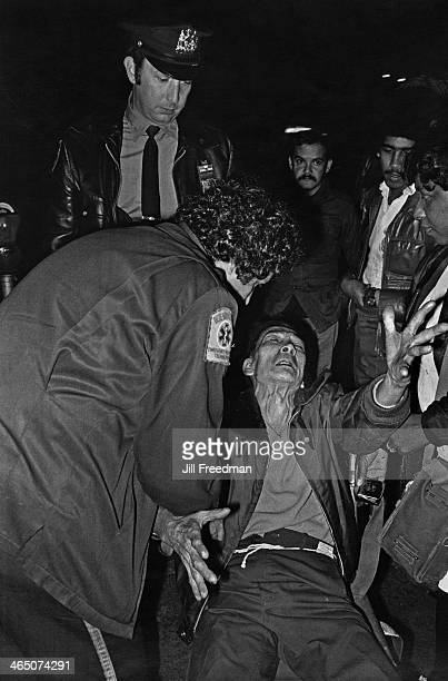 An Emergency Medical Technician of the NYPD assists a man in distress in Alphabet City Manhattan New York circa 1979