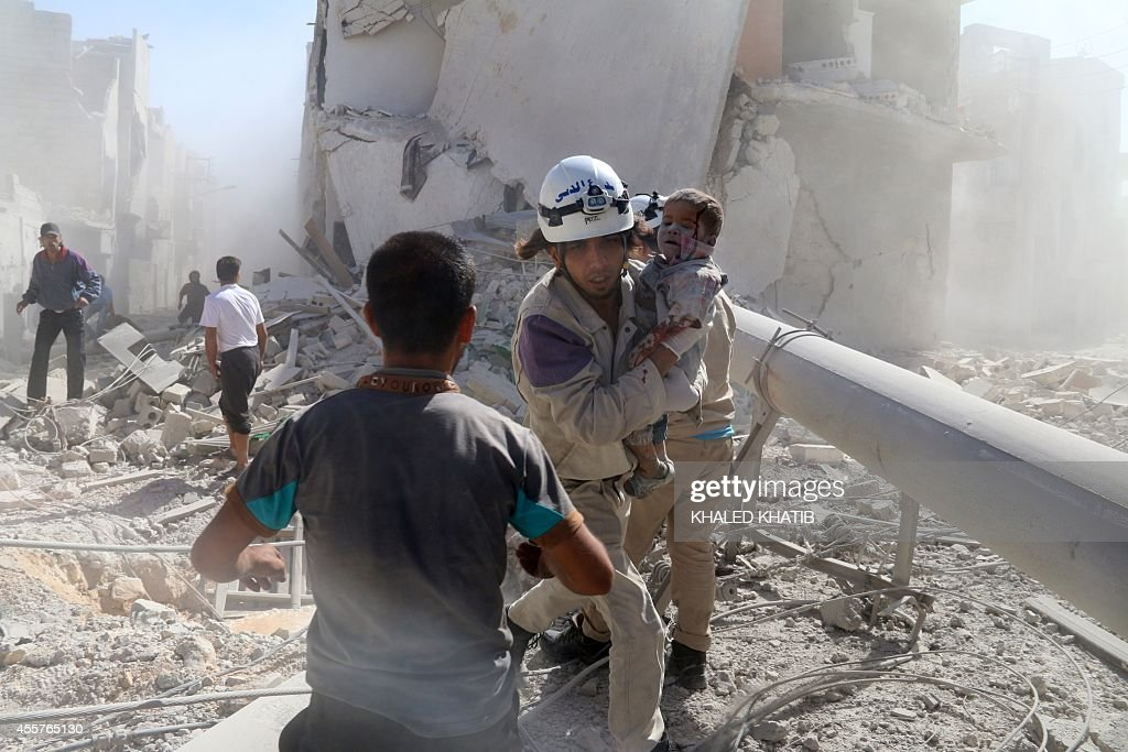 An emergency responder carries a wounded child following a reported barrel bomb strike by government forces on a rebelcontrolled district of the...