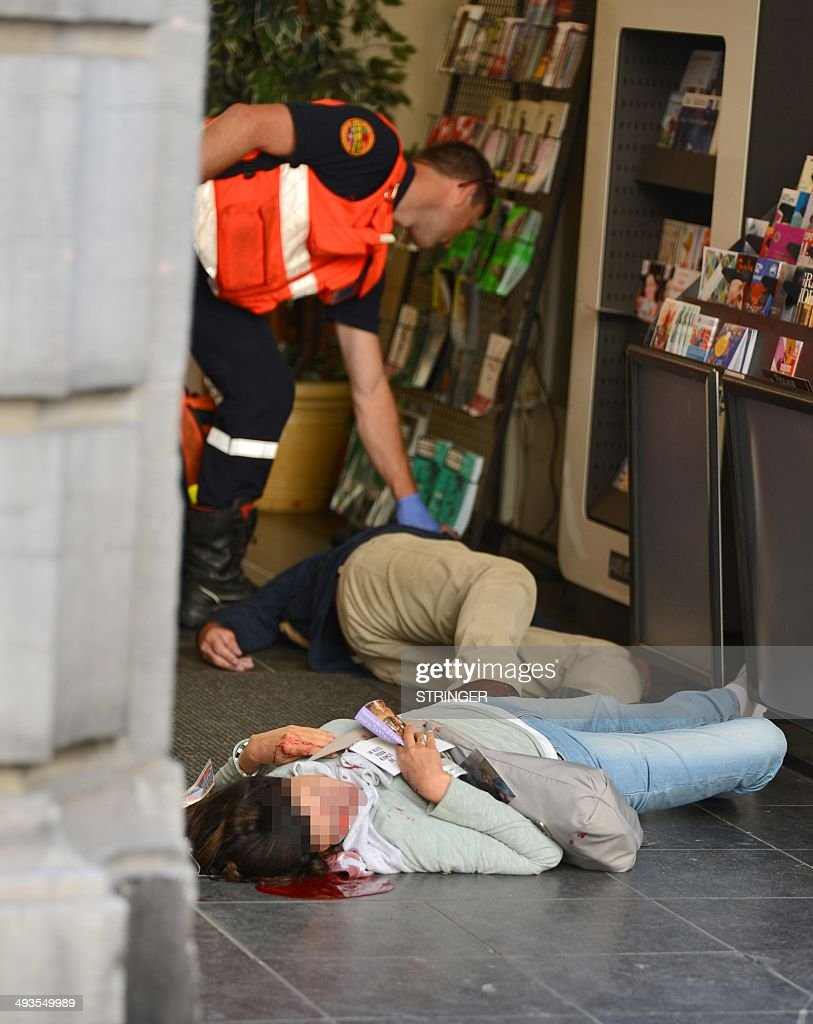 An emergency response worker checks the bodies of two victims of a shooting at a Jewish Museum in Brussels, on May 24, 2014. Three people were killed and one badly injured in a shoot-out today near the Jewish Museum in Brussels city centre, Belga news agency said, quoting firefighters' emergency services.