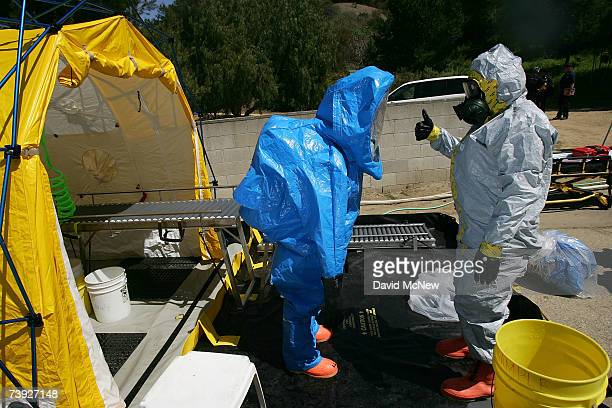 An emergency worker is decontaminated before getting out of his blue protective suit during an exercise simulating mass casualties from the collision...