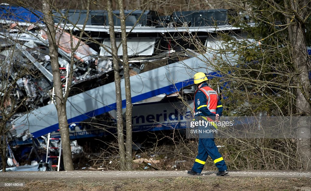 An emergency worker walks past a crashed train at the site of a train accident near Bad Aibling, southern Germany, on February 9, 2016. Two Meridian commuter trains operated by Transdev collided head-on near Bad Aibling, around 60 kilometres (40 miles) southeast of Munich, killing at least nine people and injuring around 100, police said. The cause of the accident was not immediately clear. / AFP / dpa / Sven Hoppe / Germany OUT