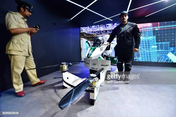 An Emiratee police officer stands next to a drone motorcycle at the Gitex 2017 exhibition at the Dubai World Trade Center in Dubai on October 8 2017...