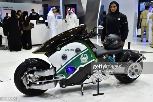 An Emiratee police officer stands next to a motorcycle at the Gitex 2017 exhibition at the Dubai World Trade Center in Dubai on October 8 2017 / AFP...