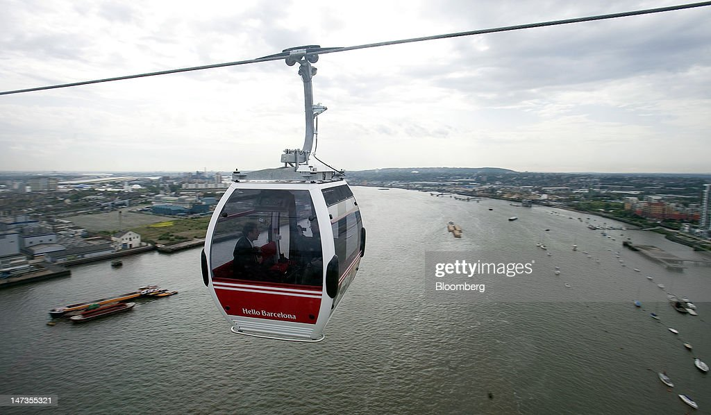 An Emirates Air Line cable car carries passengers across the River Thames on the opening day of the new transport link in London, U.K., on Thursday, June 28, 2012. The cable car system, operated by Emirates, will run between Greenwich Peninsula and the Royal Victoria Docks. Photographer: Simon Dawson/Bloomberg via Getty Images