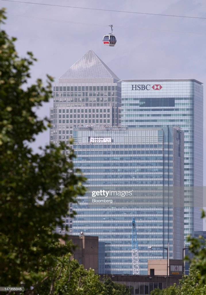 An Emirates Air Line cable car passes No. 1 Canada Square, or Canary Wharf Tower, left, Barclays Plc's headquarters, center, and the headquarters of HSBC Holdings Plc, on the opening day of the new transport link crossing above the River Thames, in London, U.K., on Thursday, June 28, 2012. The cable car system, operated by Emirates, will run between Greenwich Peninsula and the Royal Victoria Docks. Photographer: Simon Dawson/Bloomberg via Getty Images