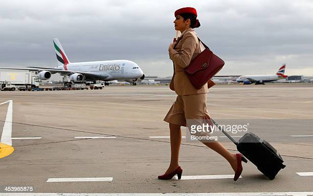 An Emirates air stewardess pulls a luggage case as she walks across the tarmac near one of the airline's Airbus A380 aircraft at Terminal 3 of...