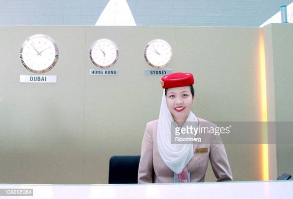 An Emirates Airline employee stands at a checkin desk in Terminal 3 at the Dubai International Airport in Dubai United Arab Emirates on Tuesday Nov 9...