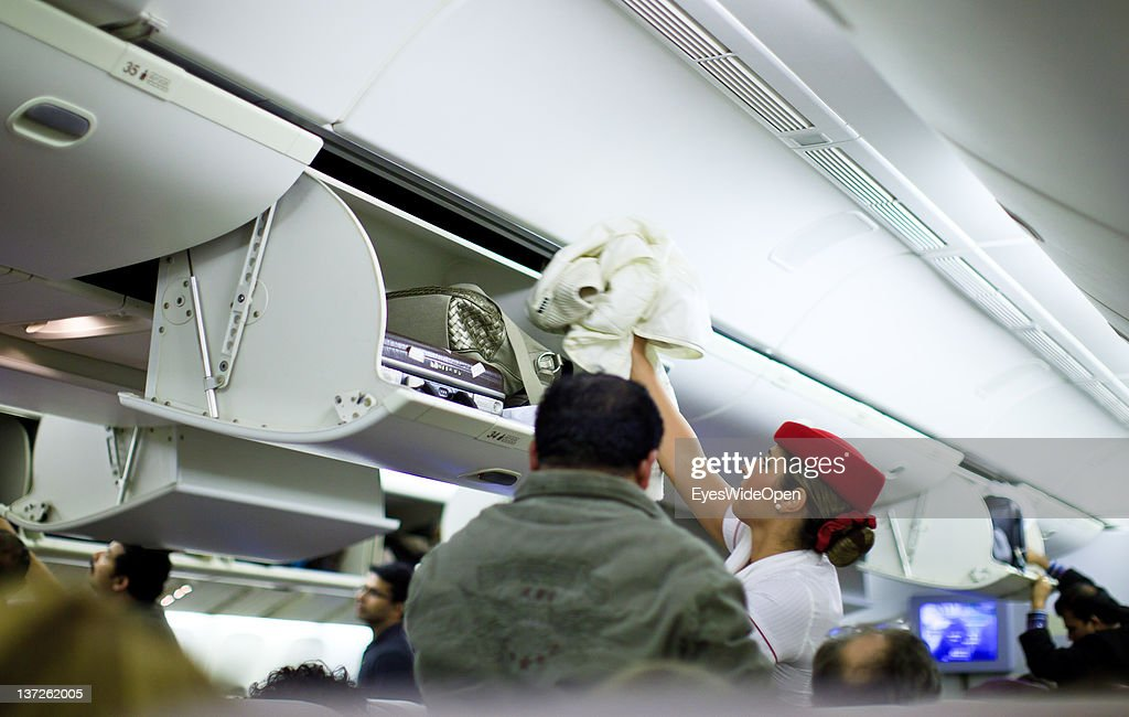 An Emirates Airline stewardess airline helps a businessman with his special handluggage, suitcase to lift it up into the baggage compartement on November 23, 2011 in Cochin, Kerala, India