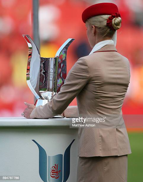 An Emirates Airlines air stewardess places the Emirates Cup Trophy on the stand