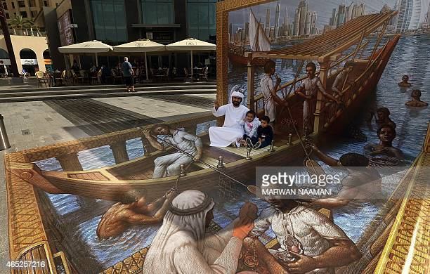 An Emirati and his children sit on a 3D artwork by US artist Kurt Wenner on March 4 2015 near the Jumeirah Beach Residence in Dubai during the Canvas...