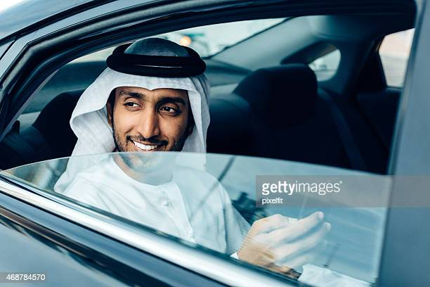 An Emirati businessman on his phone in a car