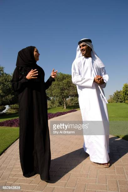 An Emirati couple walking in a park.