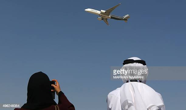 An Emirati couple watches the new Airbus A350 during a flight display at the Dubai airshow in Dubai on November 8 2015 Dubai Airshow took off today...