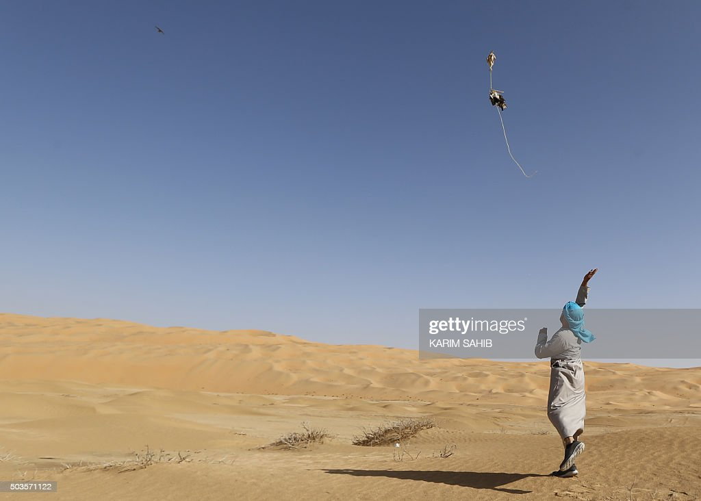 An Emirati falconer uses a lure to train his bird on January 6, 2016, during the Liwa 2016 Moreeb Dune Festival in the Liwa desert, some 250 kilometres southwest of Abu Dhabi. The festival, which attracts participants from around the Gulf region, includes a variety of races (cars, bikes, falcons, camels and horses) or other activities aimed at promoting the country's folklore.