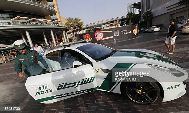 An Emirati female police officer gets out of a Ferrari police vehicle on April 25 2013 in the Gulf emirate of Dubai Dubai police showed off a new...