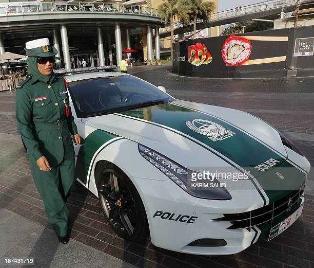An Emirati female police officer poses near a Ferrari police vehicle on April 25 2013 in the Gulf emirate of Dubai Dubai police showed off a new...