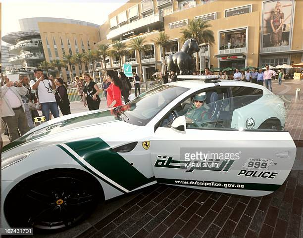 An Emirati female police officer poses sitting in a Ferrari police vehicle on April 25 2013 in the Gulf emirate of Dubai Dubai police showed off a...