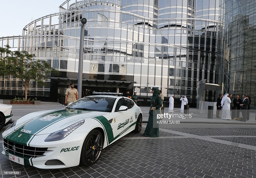 An Emirati female police officer stands near a Ferrari police vehicle at the foot of the Burj Khalifa tower in the Gulf emirate of Dubai on April 25, 2013. Two weeks after introducing the Lamborghini police car, Dubai Police has introduced a Ferrari to the fleet, to further strengthen the 'image of luxury and prosperity' of the emirate. AFP PHOTO / KARIM