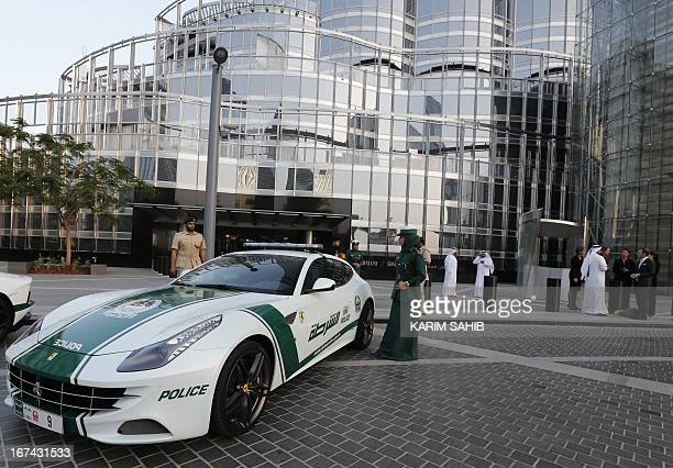 An Emirati female police officer stands near a Ferrari police vehicle at the foot of the Burj Khalifa tower in the Gulf emirate of Dubai on April 25...