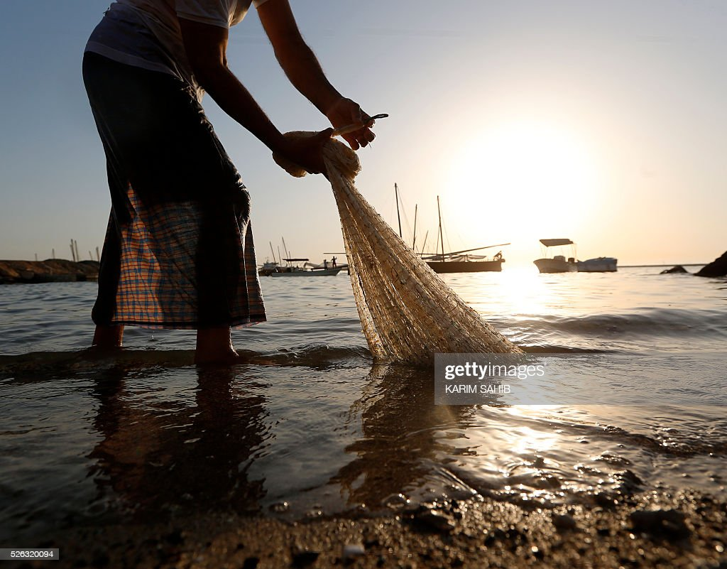 An Emirati fisherman pulls his net on al-Mirfa beach, outside Abu Dhabi on April 30, 2016 during the al-Gharbia Watersports festival. / AFP / KARIM