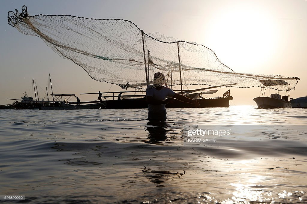 An Emirati fisherman throws his net on al-Mirfa beach, outside Abu Dhabi on April 30, 2016 during the al-Gharbia Watersports festival. / AFP / KARIM