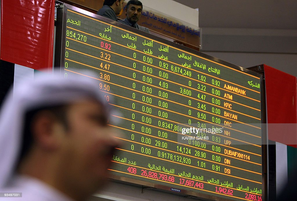 An Emirati man follows the market's movement on a monitor at the Dubai Financial Market in the Gulf emirate on November 30 2009 Stock markets in...