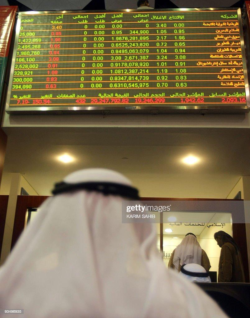 An Emirati man follows the market's movement on monitors at the Dubai Financial Market in the Gulf emirate on November 30 2009 Stock markets in Dubai...