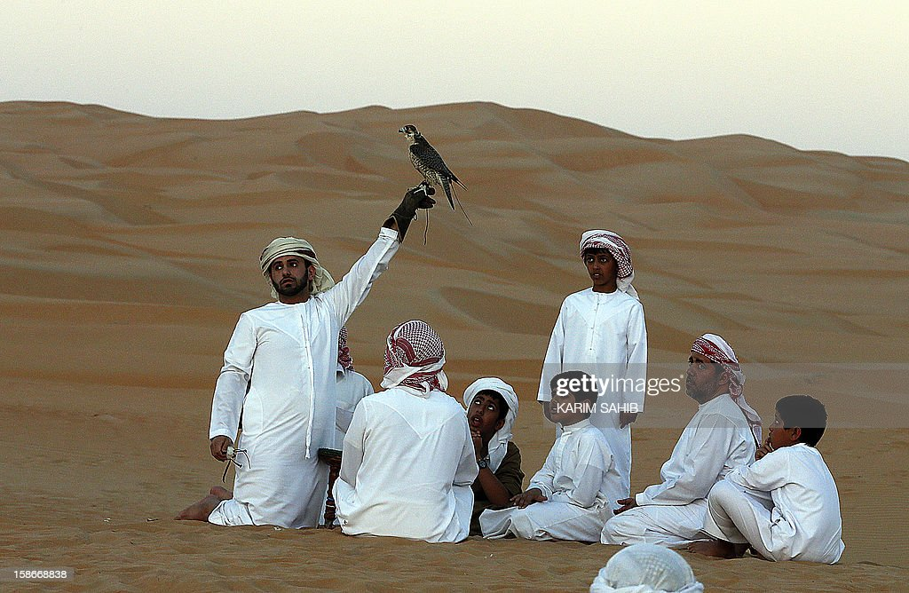 An Emirati man holds a falcon as children watch at the Liwa Desert, 220 kms west of Abu Dhabi, on the sidelines of the Mazayin Dhafra Camel Festival on December 23, 2012. The festival, which attracts participants from around the Gulf region, includes a camel beauty contest, a display of UAE handcrafts and other activities aimed at promoting the country's folklore. AFP PHOTO/KARIM SAHIB