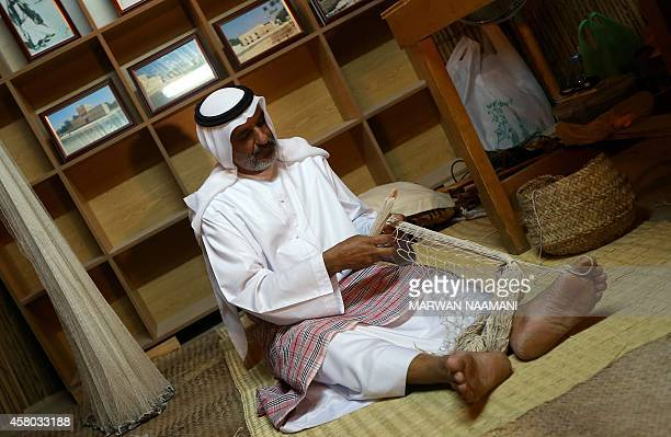 An Emirati man makes a net used by pearl divers late on October 28 2014 during a festival in the city of AlAin celebrating traditional culture...