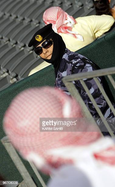 An Emirati man walks past a policewoman at the AlAin International Aerobatics Show at the Gulf emirate's airport on January 27 2010 AFP PHOTO/Karim...