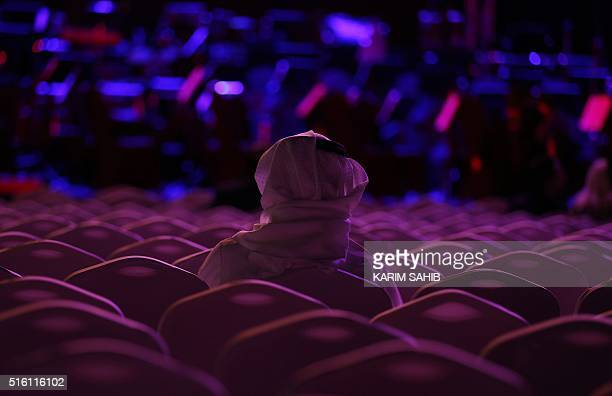 TOPSHOT An Emirati man watches a concert conducted by Germanborn music conductor Christoph Eschenbach leading an orchestra playing local Gulf...