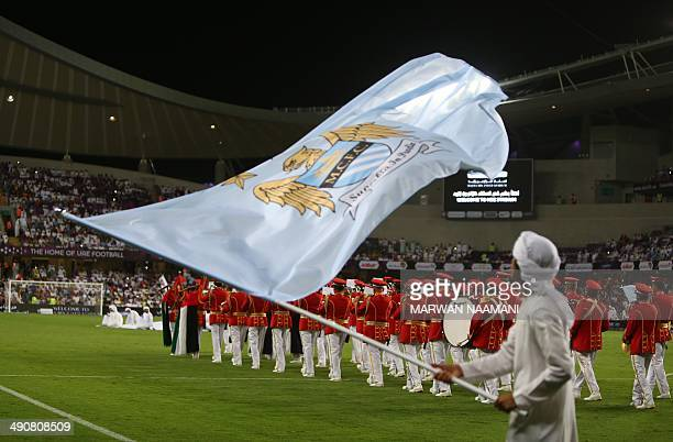 An Emirati man waves the flag of newlycrowned English Premier League champions Manchester City football club prior to their friendly match against...