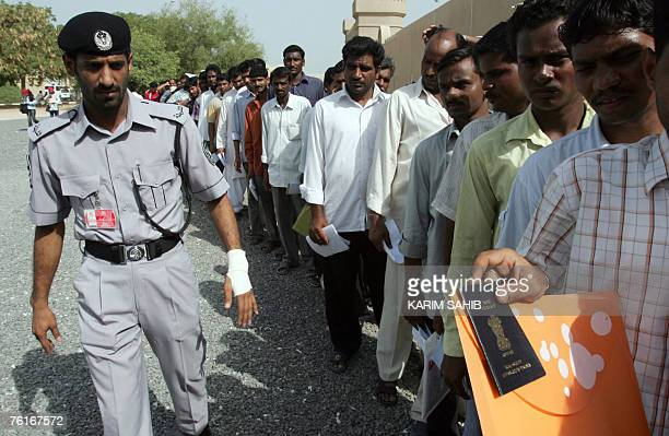 An Emirati policeman organises a line of illegal workers mostly Asians queuing with their passports and papers outside the Dubai immigration office...