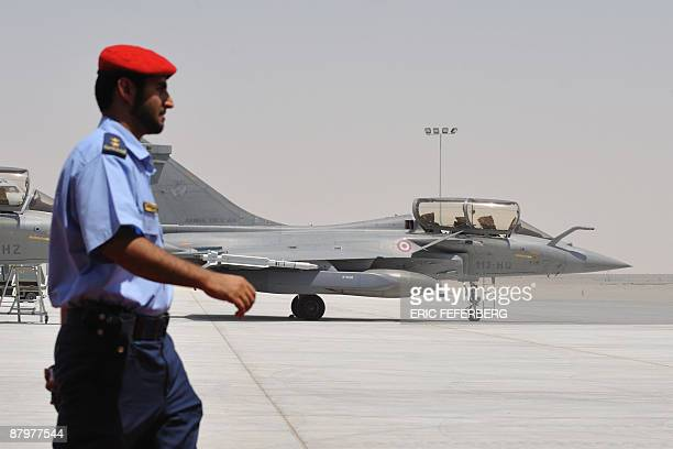 An Emirati soldier walks past a Rafales French jet fighter at a military base near Abu Dhabi on May 25 2009 French President Nicolas Sarkozy travels...