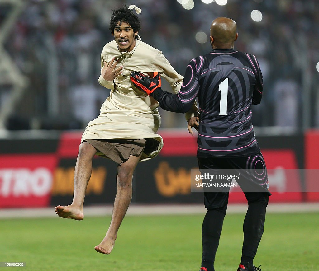 An Emirati supporter jumps towards Ali Khussef Hamid, United Arab Emirates' goalkeeper after storming the pitch during the 21st Gulf Cup's final between United Arab Emirates and Iraq on January 18, 2013 in Manama. United Arab Emirates won 2-1 against Iraq.