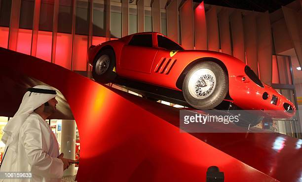 An Emirati visitor looks at a Ferrari displayed at the Ferrari theme park during its media launch in the Emirati capital of Abu Dhabi on October 27...