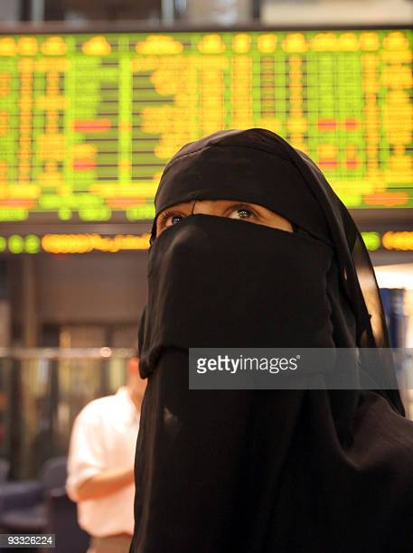 An Emirati woman trader watches the quotation board at the Abu Dhabi stock exchange 07 June 2006 in Abu Dhabi AFP PHOTO/STR