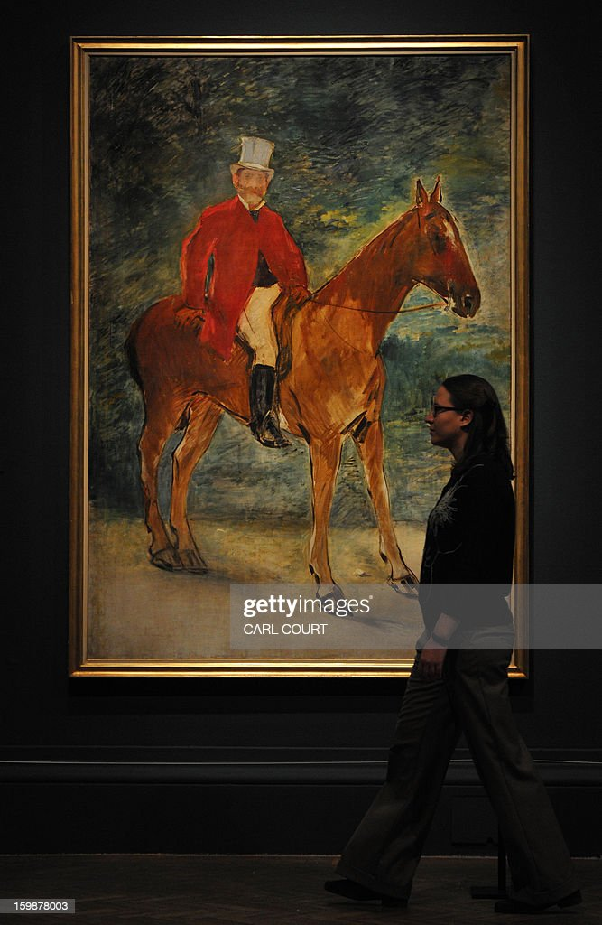 An emlpoyee poses next to a painting by French artist Edouard Manet entitled 'Portrait of M. Arnaud (The Rider)' at the Royal Academy of Arts in central London on January 22, 2013. Forming part of the 'Manet: Portraying Life' exhibition, it is due to be displayed from January 26 to April 14.