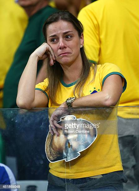 An emotional Brazil fan reacts while holding a Neymar mask after being defeated by Germany 71 during the 2014 FIFA World Cup Brazil Semi Final match...