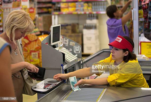 An employee accepts ruble notes as payment for a customer's goods at a checkout desk in an OAO Magnit store in Krasnodar Russia on Friday Aug 17 2012...