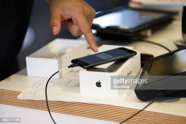 An employee activates an Apple Inc iPhone for a customer at an ATT Inc store in Newport Beach California US on Thursday Aug 10 2017 ATT Inc shares...