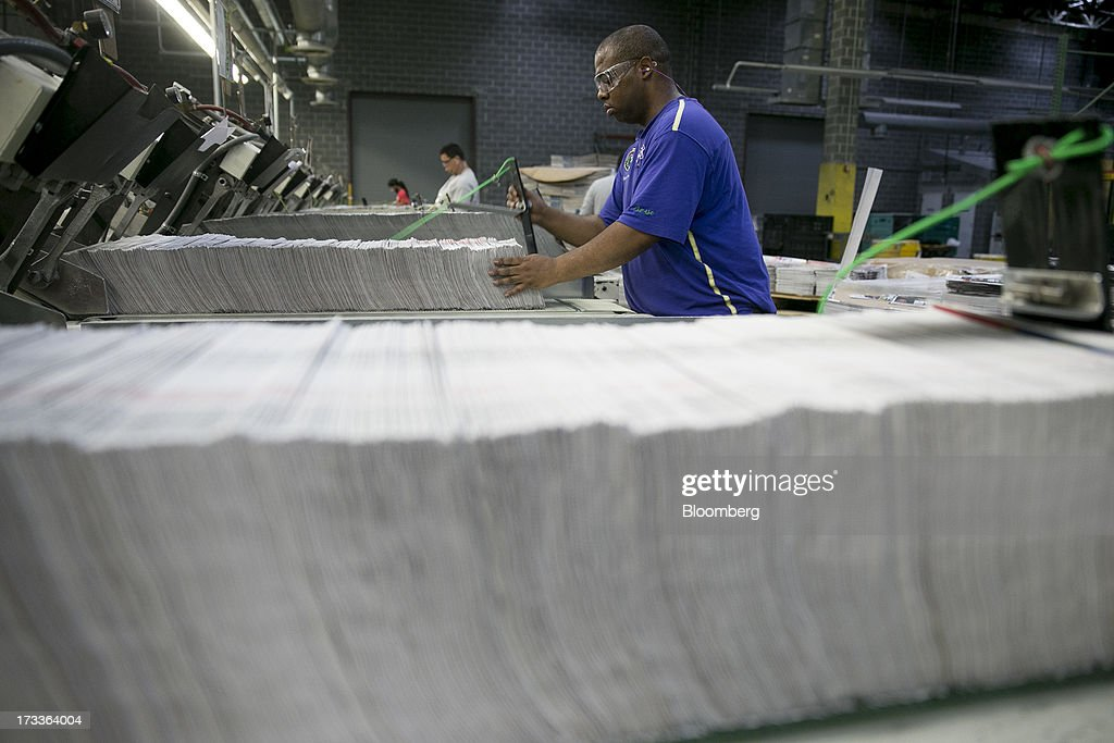 An employee adds advertisement insets into a collator machine at the Washington Post newspaper production facility in Springfield, Virginia, U.S., on Friday, July 12, 2013. The Washington Post began publishing on Thursday, Dec. 6, 1877, and had a circulation of 10,000. The newspaper contained four pages and cost three cents a copy. Photographer: Andrew Harrer/Bloomberg via Getty Images