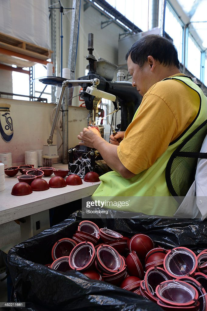 An employee adds stitching to leather casings for red cricket balls at the Kookaburra Sports Pty Ltd. plant in Melbourne, Australia, on Tuesday, Nov. 26, 2013. Australian businesses need to boost efficiency to maintain growth in living standards, Reserve Bank of Australia Deputy Governor Philip Lowe said. Photographer: Carla Gottgens/Bloomberg via Getty Images