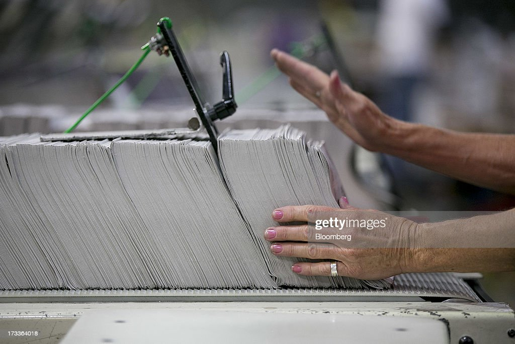 An employee adds TV week insets into to a collator machine at the Washington Post newspaper production facility in Springfield, Virginia, U.S., on Friday, July 12, 2013. The Washington Post began publishing on Thursday, Dec. 6, 1877, and had a circulation of 10,000. The newspaper contained four pages and cost three cents a copy. Photographer: Andrew Harrer/Bloomberg via Getty Images