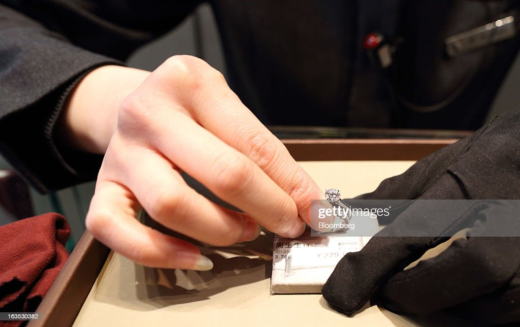An employee adjusts a diamond ring at the Chow Sang Sang Holdings International Ltd. jewelry store in the Sanlitun district of Beijing, China, on Monday, March 11, 2013. China's consumer prices climbed 3.2 percent from a year earlier, according to figures released March 9, exceeding January's 2 percent gain and the median estimate for a 3 percent increase in a Bloomberg survey of analysts. Photographer: Tomohiro Ohsumi/Bloomberg via Getty Images