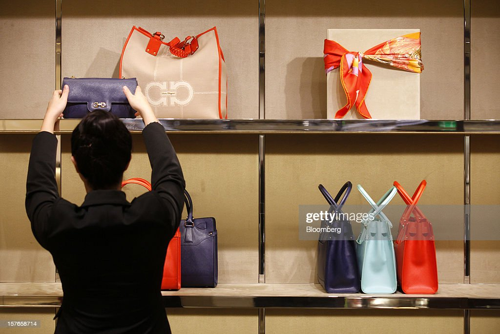 An employee adjusts a display of ladies handbags in this arranged photograph inside Salvatore Ferragamo SpA's Sloane Street store in London, U.K., on Wednesday, Dec. 5, 2012. Demand for Ferragamo's shoes and other items is increasing even as China's economy slows and Europe's debt crisis weighs on consumer spending. Photographer: Simon Dawson/Bloomberg via Getty Images