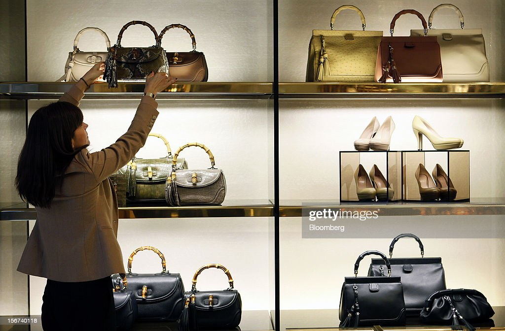 An employee adjusts a display of luxury bags and shoes inside a Gucci store, a luxury unit of France's PPR SA, in Rome, Italy, on Monday, Nov. 19, 2012. PPR SA, the French owner of the Gucci and Puma brands, said it's confident of revenue and profit growth in 2012. Photographer: Alessia Pierdomenico/Bloomberg via Getty Images