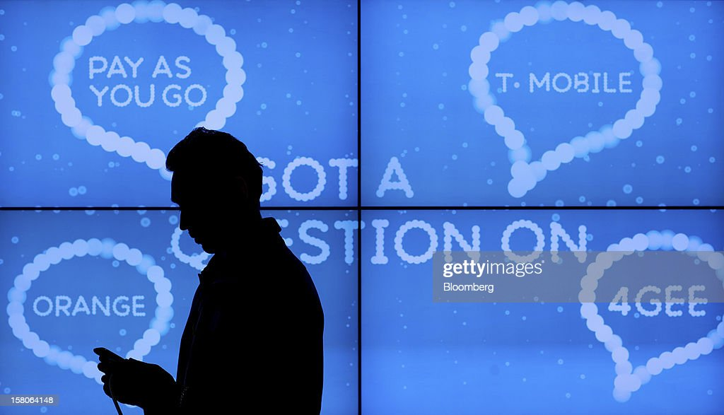 An employee adjusts a handset displayed in front of a giant screen advertising the T-Mobile and Orange mobile phone networks inside a EE (Everything Everywhere) store, a joint venture between France Telecom SA and Deutsche Telekom AG, in Stratford, U.K., on Monday, Dec. 5, 2012. France Telecom CEO Stephane Richard said in an interview last month that the Paris-based company has received interest from private-equity firms seeking a minority stake in the 50-50 venture, and may also consider an initial public offering of the unit. Photographer: Jason Alden/Bloomberg via Getty Images