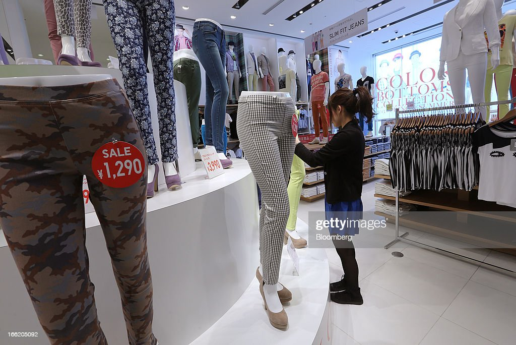 An employee adjusts a pair of pants displayed on a mannequin at Fast Retailing Co.'s Uniqlo store in the Ginza district of Tokyo, Japan, on Wednesday, April 10, 2013. Fast Retailing, Asia's largest apparel retailer, is scheduled to announce earnings tomorrow. Photographer: Yuriko Nakao/Bloomberg via Getty Images
