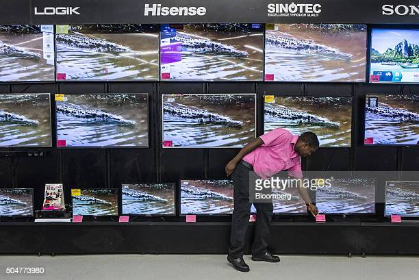 An employee adjusts a price sign on a display of flat screen televisions for sale in a Game supermarket operated by Massmart Holdings Ltd at the...